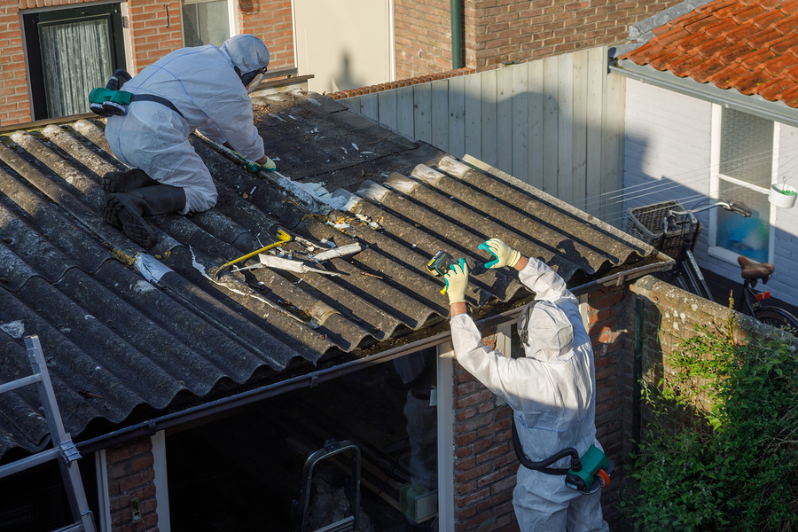 men in protective suit removing asbestos cement